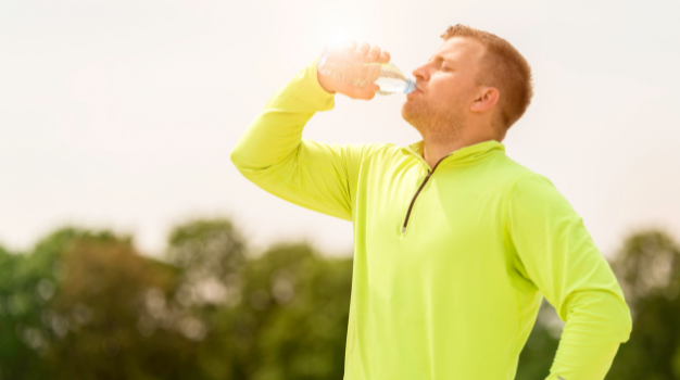 A man wearing a yellow sports shirt keeps hydrated by drinking water from a bottle on a hot sunny day